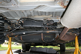 evaporative charcoal canister on a 2001 Toyota Sienna is located under a plastic shield